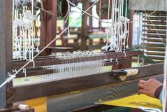 Weave silk cotton on the manual wood loom. In Thailand ,The process of silk weaving in the production of Thai silk royalty free stock images