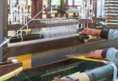 Weave silk cotton on the manual wood loom. In Thailand ,The process of silk weaving in the production of Thai silk stock photos