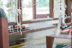 Weave silk cotton on the manual wood loom. In Thailand ,The process of silk weaving in the production of Thai silk royalty free stock photos