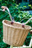 Weaved basket in front of foldable bicycle with plant background. Enjoy activity Stock Image