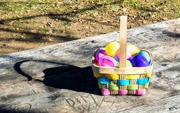 Wicker Easter basket filled with colorful eggs stock photos