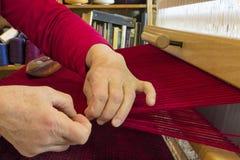 Weaver Adjusts Edge av tyg som hon väver Fotografering för Bildbyråer