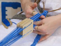 Weaving. A woman waving with blue yarn Royalty Free Stock Photo