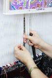 Weaving. Woman hands weaving a carpet Stock Images