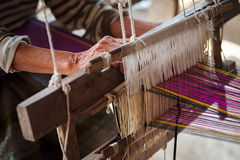 Weaving. Close up of old woman weaving blue and white pattern on loom Royalty Free Stock Photography