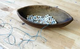 Weaving of beads. Closeup blue beads in a wooden bowl shaped like a boat on a wooden table. Weaving of beads. Blue beads in a wooden bowl shaped like a boat on Stock Photos