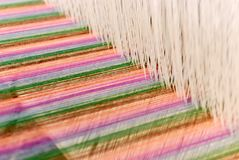 Weaving colorful cotton threads by tradtional wooden loom Royalty Free Stock Photography