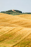 Weaving field, and house on top of a hill in Tuscany, Italy Stock Image