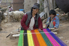Weaving Indian woman in domestic environment. Bolivia: group portrait of Native American, Indian woman in traditional clothing, working at a loom with het son Royalty Free Stock Photo