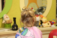 Weaving little blonde girl's braids in a hair salon. Stock Photos