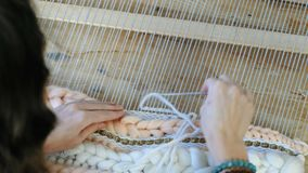 Weaving on a loom. Closeup woman`s hands running on a loom. Threading the needle through the strands of frame and fasten. Closeup woman`s hands running on a loom stock video footage