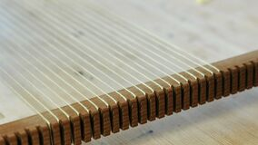 Weaving on a loom frame. Closeup woman`s hand puts the thread in the frame for weaving. Weaving on a loom frame. Closeup woman`s hand puts the thread in the stock video footage