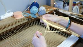 Weaving on a loom frame. Closeup woman`s hands spool of yellow thread on the shuttle. Weaving on a loom frame. Closeup woman`s hands spool of yellow thread on stock video footage
