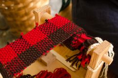 Weaving loom with knitted throw muffler red and brown.  royalty free stock images