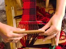 Weaving loom with knitted throw muffler red and brown in process. With hands in wirking royalty free stock image