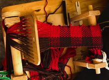 Weaving loom with knitted throw muffler red and brown view above. Weaving loom with knitted throw muffler red and brown in process stock images
