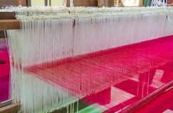 Weaving loom and shuttle on the warp royalty free stock photo