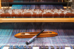 Weaving shuttle on the blue warp in weaving machine Stock Image