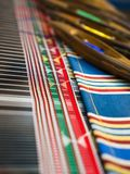 Weaving shuttles and colorful textile with pattern Royalty Free Stock Photography