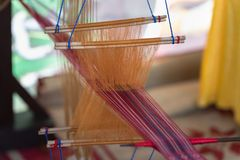 Weaving silk in traditional way with manual loom in Vietnam, closeup Royalty Free Stock Image