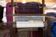Weaving silk in traditional way with manual loom in Vietnam, closeup Royalty Free Stock Photo