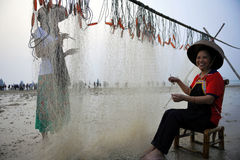 Weaving Webs Happily. The fishermen still weave fishing nets by the traditional manual Royalty Free Stock Photos