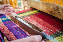 Weaving on a wooden loom Stock Photo