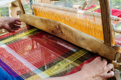 Weaving on a wooden loom Stock Image