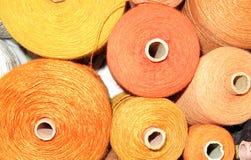 Weaving yarn in yellow tones on spools stock image