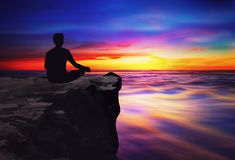 Yoga man silhouette meditating at sunset colorful sky and water reflection royalty free stock photo