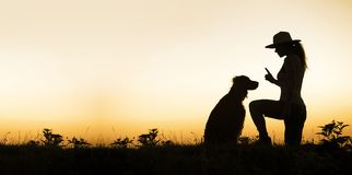 Dog and his trainer - silhouette image with blank, copy space. Web banner of a dog and his female trainer - silhouette image with blank, copy space Stock Photos