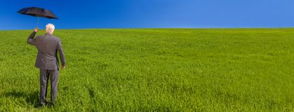 Web banner panoramic business concept photograph of a businessman standing in a green field under a bright blue sky holding and royalty free stock photo