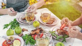 Web banner. People eat at the table with wine, grilled fish, fresh vegetables and herbs. Horizontal shot royalty free stock image