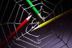 Web Design. Concept. Three color pencils in rope web on dark background royalty free stock photo