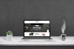 Web design agency presentation with responsive, flat web site design on laptop display. Cup of coffee and plat beside. Black wall in background royalty free stock photo