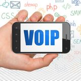 Web design concept: Hand Holding Smartphone with VOIP on display. Web design concept: Hand Holding Smartphone with  blue text VOIP on display,  Hand Drawn Site Stock Photo