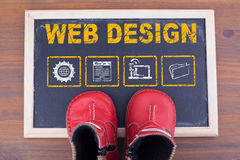 Web Design. Kid shoes on chalkboard and wooden backgroundn Stock Photo