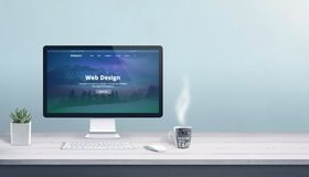 Web design studio with computer display, keyboard and mouse on office work desk. Modern flat design web page on display royalty free stock images