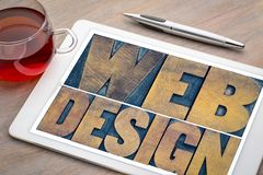 Web design word abstract on a digital tablet. Web design word abstract - textin vintage letterpress wood type printing blocks on a digital tablet with cup of tea Stock Image