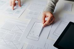 Web designer creating mobile responsive website. Website wireframe sketches on white table stock images