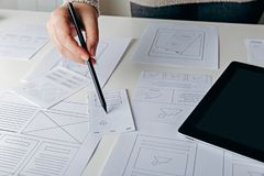 Web designer creating mobile responsive website. Website wireframe sketches on white table royalty free stock images