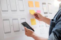 Web designer planning application for mobile phone. Web designer, UX UI designer planning application for mobile phone Stock Image