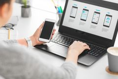 Web designer with smartphone and laptop at office stock photos