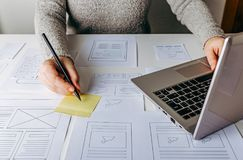 Web designer working at laptop and website wireframe sketches. On white table stock photography