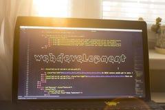 Web development phrase ASCII art inside HTML code. Web developer workplace in sunset lights Royalty Free Stock Images