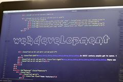 Web development phrase ASCII art inside real HTML code. Web developing concept on screen. Abstract information technology modern background. Laptop in sunset Royalty Free Stock Photography