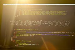 Web development phrase ASCII art inside real HTML code. Web developing concept on screen. Abstract information technology modern background. Laptop in sunset Stock Photo