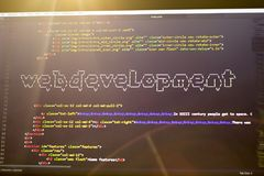Web development phrase ASCII art inside real HTML code. Web developing concept on screen. Abstract information technology modern background. Laptop in sunset Stock Image