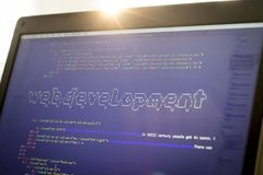 Web development phrase ASCII art inside real HTML code. Web developing concept on screen. Abstract information technology modern background. Laptop in sunset Stock Photos