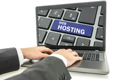 Web hosting. Closeup of male hands working on laptop computer with web hosting button on its screen Royalty Free Stock Photos